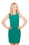 La belle blonde dans la robe verte a ses mains sur la taille Photographie stock