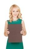 La belle blonde dans la robe verte tient une boîte Images stock