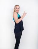 La belle blonde dans une chemise de sports, des shorts noirs et des espadrilles colorées pose, montrant manie maladroitement vers Images stock