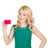 La belle blonde dans une robe verte tient une carte Photos libres de droits