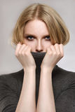 La belle blonde dans une veste grise ferme des mains de lèvres Photographie stock libre de droits
