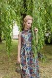 La belle blonde de fille d'offre de bonbon avec des yeux bleus se tient près d'un arbre avec de longues branches avec un brin des Photo stock