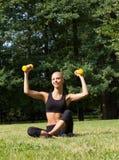 La belle blonde en parc avec des haltères Image stock