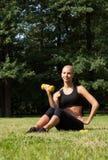 La belle blonde en parc avec des haltères Photographie stock libre de droits