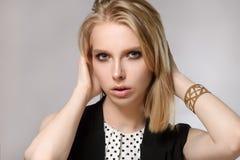 La belle blonde garde des mains près du visage Photographie stock