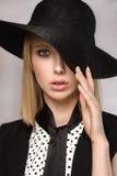 La belle blonde garde l'oeil étroit de main du chapeau un Photographie stock libre de droits
