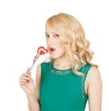 La belle blonde mord le coeur sur une fourchette Image libre de droits