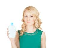 La belle blonde tient dans une main des cosmétiques d'une bouteille Photos stock