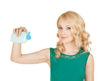 La belle blonde tient dans une main des cosmétiques d'une bouteille Photo stock