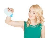 La belle blonde tient dans une main des cosmétiques d'une bouteille Image libre de droits