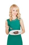 La belle blonde tient un plat avec un morceau d'un tarte de chocolat Image libre de droits
