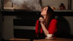 La belle brune dans une veste rouge, travaux avec son ordinateur portable et fume une cigarette électronique dans un lieu public clips vidéos