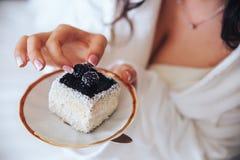 La belle brune de jeune mariée mangent le gâteau dans un peignoir photos stock