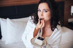 La belle brune de jeune mariée mangent le gâteau dans un peignoir Photos libres de droits