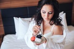 La belle brune de jeune mariée mangent le gâteau dans un peignoir Images libres de droits