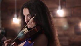 La belle brune joue le violon La fille déplace l'arc au-dessus des ficelles extrayant la musique clips vidéos