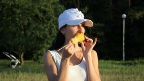 La belle brune mange du maïs, regarde dans la caméra banque de vidéos