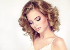 La belle brune modèle avec la longueur moyenne a courbé des cheveux et lumineux composez images libres de droits