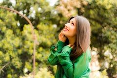 La belle brune s'est habillée dans des vêtements verts, parlant au téléphone Photo libre de droits