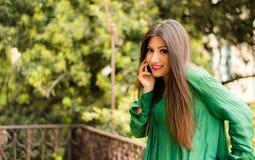 La belle brune s'est habillée dans des vêtements verts, parlant au téléphone Images stock