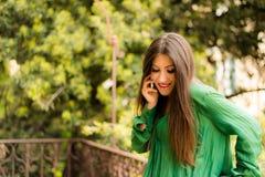 La belle brune s'est habillée dans des vêtements verts, parlant au téléphone Photographie stock libre de droits