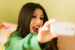 La belle brune s'est habillée dans des vêtements verts, prenant un selfie Photographie stock libre de droits