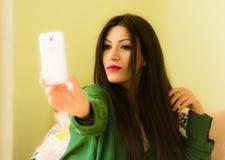 La belle brune s'est habillée dans des vêtements verts, prenant un selfie Image stock