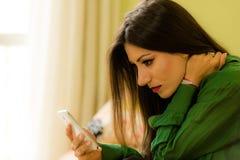 La belle brune s'est habillée dans le smartphone de regard vert Photo stock