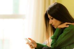 La belle brune s'est habillée dans le smartphone de regard vert Images libres de droits