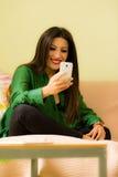 La belle brune s'est habillée dans le smartphone de regard vert Photos stock