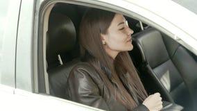 La belle brune se repose dans la voiture, regards dans le miroir et lisse clips vidéos