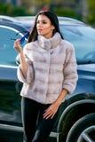 La belle brune sexy dans les lunettes de soleil et un manteau de fourrure descend la rue le jour ensoleillé et regarde loin Autom photographie stock libre de droits
