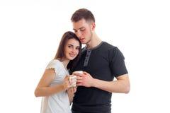 La belle brune tendre se tient avec son ami et conserve avec lui une tasse de thé Images stock