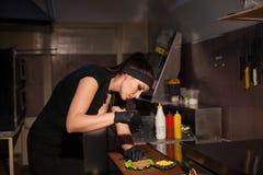 La belle cuisinière de fille prépare l'hamburger de cuisine Photos stock