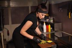 La belle cuisinière de fille prépare l'hamburger de cuisine Photographie stock libre de droits