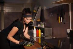 La belle cuisinière de fille prépare l'hamburger de cuisine Images stock