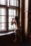 La belle dame élégante d'affaires en verres lit un livre sur le rebord de fenêtre Image stock