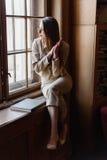 La belle dame élégante d'affaires en verres lit un livre sur le rebord de fenêtre Photos stock