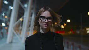 La belle dame blonde moderne dans les verres avec la jante noire et les vêtements foncés marche près du centre d'affaires dans banque de vidéos