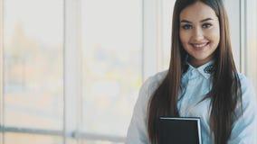 La belle dame d'affaires regarde l'appareil-photo et sourit tout en travaillant dans le bureau banque de vidéos