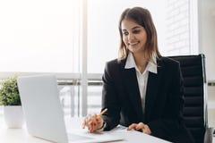 La belle dame d'affaires regarde l'ordinateur portable et sourit tout en travaillant dans le bureau Concentré sur le travail image stock