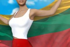 La belle dame dans la jupe lumineuse tient le drapeau de la Lithuanie dans des mains derrière son dos sur le fond de ciel nuageux illustration libre de droits
