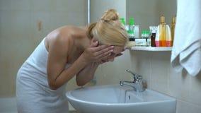 La belle dame lave le visage devant le miroir, satisfait après avoir rendu visite à l'esthéticien banque de vidéos