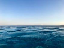 La belle eau claire naturelle azurée humide bleue contre un ciel bleu et l'horizon rayent dans une station de vacances chaude tro photo libre de droits
