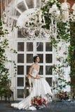 La belle et à la mode fille de modèle de brune dans la robe de mariage élégante avec les épaules nues et avec le diadème sur sa t photographie stock libre de droits