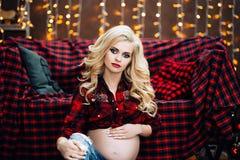 La belle et élégante femme caucasienne enceinte dans le T-shirt et des blues-jean avec les cheveux blonds tient son ventre, éléga Image stock