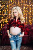 La belle et élégante femme caucasienne enceinte dans le T-shirt et des blues-jean avec les cheveux blonds tient son ventre, éléga Photo stock