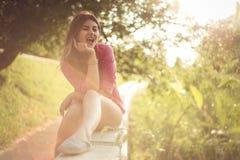 La belle et attirante femme s'asseyant d'un côté, denim occasionnel sexy de port court-circuite Photographie stock libre de droits