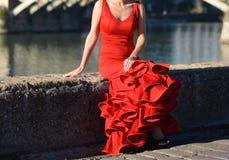 La belle et sensuelle femme dans la robe rouge de flamenco se reposant au bord de la rivière Images stock