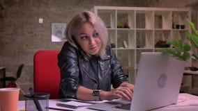 La belle femelle blonde caucasienne parle au-dessus du téléphone portable et introduit au clavier l'ordinateur portable, étant da banque de vidéos